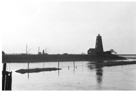 1934 photo lighthouse surrounded by tide and ship at rear